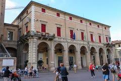 Los turistas que caminan cerca ayuntamiento Rímini en Cavour ajustan fotos de archivo