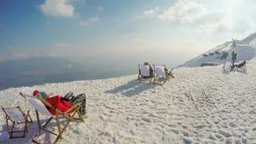 Los turistas que disfrutan de la visión desde el top de la montaña nevosa, teniendo resto en sillas, se relajan metrajes
