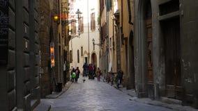 Los turistas que montan segways tragan una pequeña calle italiana en Florencia almacen de metraje de vídeo