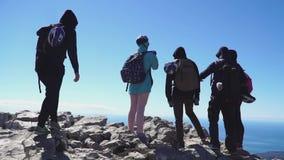 Los turistas se acercan encima de la montaña y de mirar el mar abajo, opinión de la parte posterior metrajes