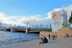 Los turistas se sientan en los pasos del embarcadero en el fondo de banderas Fotos de archivo