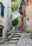 Los turistas suben a lo largo de la calle estrecha de la ciudad vieja, Kotor, Montenegr Imagen de archivo