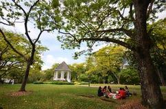 Los turistas tienen una comida campestre en estrado de la orquesta de los jardines botánicos en Singapur Foto de archivo