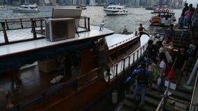 Los turistas toman el barco en la bahía de Kowloon en un transbordador en el puerto de Hong Kong almacen de metraje de vídeo