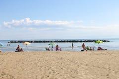 Los turistas toman el sol en la playa en el puerto deportivo de Bellaria Igea, Rímini Foto de archivo