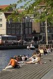 Los turistas toman un baño del sol en los bancos de un canal en Amsterdam durante un día de primavera Fotos de archivo libres de regalías