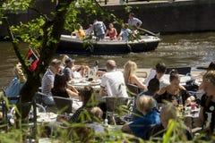 Los turistas toman una bebida en el sol en la terraza de un café en los bancos de un canal en Amsterdam Imágenes de archivo libres de regalías