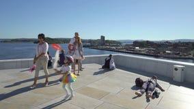 Los turistas y los locals admiran las vistas de Oslo del tejado del nuevo edificio del teatro de la ópera nacional almacen de video