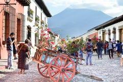 Los turistas y los locals dan un paseo las calles de la piedra del adoquín de la ciudad colonial hermosa de Antigua en un día sol Imagen de archivo