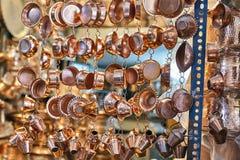 Los utensilios de cobre amarillo brillantes se suspenden en la tienda de la loza, Yazd, Irán fotografía de archivo libre de regalías