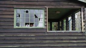 Los vándalos tienen ventanas quebradas en una casa vieja Foto de archivo libre de regalías