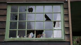 Los vándalos tienen ventanas quebradas en una casa vieja Imagen de archivo libre de regalías