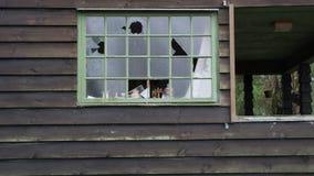 Los vándalos tienen ventanas quebradas en una casa vieja Imágenes de archivo libres de regalías