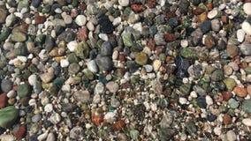Los vídeos como el agua clara en la playa lavan los guijarros coloreados metrajes