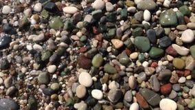 Los vídeos como el agua en la playa lavada colorearon los guijarros hermosos finos almacen de metraje de vídeo