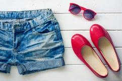 Los vaqueros calzan las gafas de sol para la muchacha adolescente en el piso de madera blanco Fotos de archivo libres de regalías