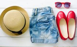 Los vaqueros calzan las gafas de sol para la muchacha adolescente en el piso de madera blanco Foto de archivo libre de regalías