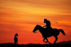 Los vaqueros siluetean en la puesta del sol stock de ilustración