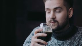 Los varones que sostienen las botellas de la cerveza, taza de cerveza y lo beben con el placer, risa sorprendida con el resultado metrajes