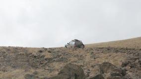 Los vehículos campo a través expedicionarios montan lentamente en el camino rocoso de la montaña almacen de metraje de vídeo