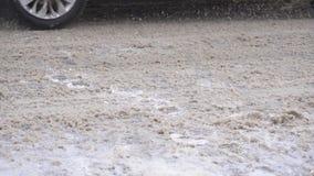 Los vehículos conducen en el camino del invierno asperjado con la sal y los reactivo, cámara lenta del camino almacen de metraje de vídeo