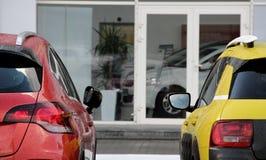 Los vehículos de alquiler coloreados acercan a la foto de la acción de la oficina del alquiler del coche Imagen de archivo libre de regalías