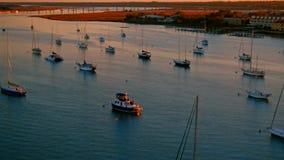 Los veleros anclados en un río por una ciudad aúllan en la puesta del sol caliente almacen de video