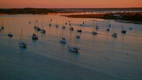 Los veleros anclados en un río por una ciudad aúllan en la puesta del sol caliente metrajes