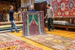 Los vendedores de la alfombra pusieron una demostración Foto de archivo