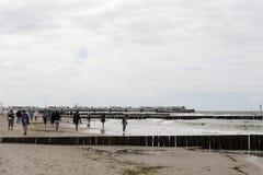 Los veraneantes gozan el caminar en una playa de la arena Fotos de archivo