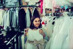 Los vestidos de examen del cliente adolescente en paños de los children's hacen compras Foto de archivo