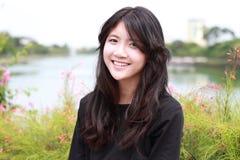Los vestidos hermosos adolescentes del negro de la muchacha del estudiante tailandés se relajan y sonríen Fotografía de archivo