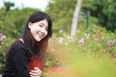 Los vestidos hermosos adolescentes del negro de la muchacha del estudiante tailandés se relajan y sonríen Imagen de archivo