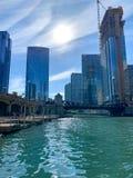 Los viajeros acometen el hogar en el riverwalk a lo largo de un río Chicago brillante foto de archivo