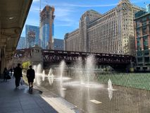 Los viajeros caminan a lo largo de una fuente del splashpad en el riverwalk del río Chicago imagen de archivo
