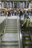 Los viajeros del tren de Amtrak se colocan en línea bajo salidas firman, mientras que un hombre va abajo de la escalera móvil en  Imagen de archivo