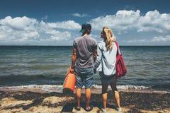 Los viajeros hombre y mujer de los pares que se colocan en viaje de la aventura de la costa relajan concepto fotografía de archivo libre de regalías