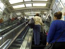 Los viajeros montan la escalera móvil escarpada en el aeropuerto de Chicago ÓHarez Foto de archivo libre de regalías