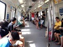 Los viajeros o los pasajeros dentro del MRT pasan el tiempo jugando a los juegos, vídeos de observación, comprobando su correo el Imagen de archivo