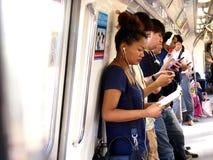 Los viajeros o los pasajeros dentro del MRT pasan el tiempo jugando a los juegos, vídeos de observación, comprobando su correo el Foto de archivo