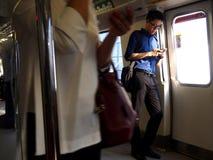 Los viajeros o los pasajeros dentro del MRT pasan el tiempo jugando a los juegos, vídeos de observación, comprobando su correo el Fotografía de archivo libre de regalías
