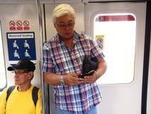 Los viajeros o los pasajeros dentro del MRT pasan el tiempo jugando a los juegos, vídeos de observación, comprobando su correo el Fotografía de archivo