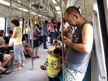 Los viajeros o los pasajeros dentro del MRT pasan el tiempo jugando a los juegos, vídeos de observación, comprobando su correo el Fotos de archivo libres de regalías
