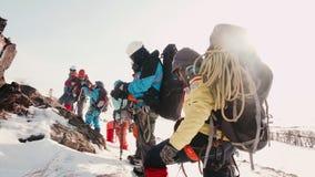 Los viajeros pararon en el pie de la montaña y la mirada en el top que se preguntaba cómo levantarse allí almacen de video