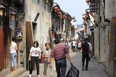 Los viajeros que caminan la calle estrecha Fotos de archivo libres de regalías