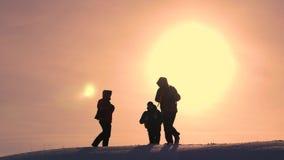 Los viajeros se encuentran en una colina nevosa y disfrutan en la victoria contra el contexto de un sol amarillo hermoso Trabajo  almacen de video