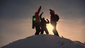 Los viajeros vienen al top de la colina nevosa y disfrutan en la victoria contra el contexto de una puesta del sol amarilla Traba almacen de metraje de vídeo