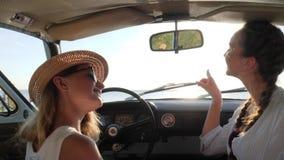 Los viajes del coche, fueron con nosotros en el coche, muchacha dos en el automóvil en luz del sol, hembras en el auto en la natu almacen de metraje de vídeo