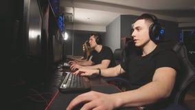 Los videojugadores alegres del e-deporte celebran la victoria en los ordenadores potentes en centro del juego almacen de metraje de vídeo