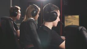 Los videojugadores casuales recolectan juntos en club del juego de la PC para competir en el torneo en línea almacen de metraje de vídeo